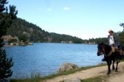 Horse riding past mountain lakes