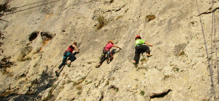 Children rock climbing on family adventure holiday