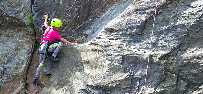 Young girl rock climbing family adventure holiday